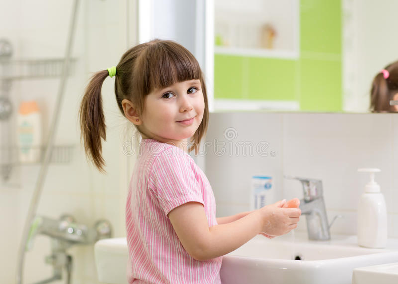 Cute kid girl with ponytail in pink bathrobe washing her hands. royalty free stock photo