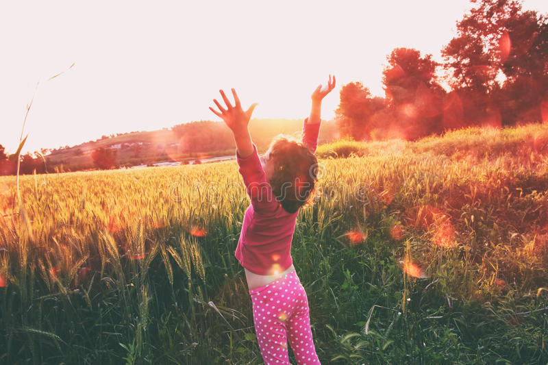 Cute kid (girl) standing in field at sunset with hands stretched looking at the landscape. instagram style image with bokeh lights stock image