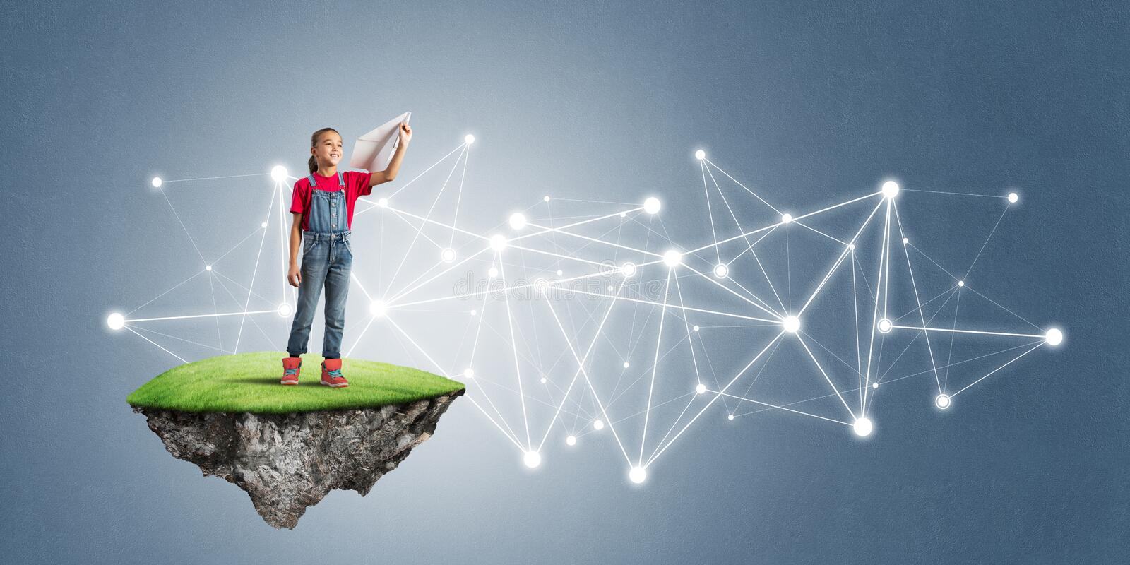 Concept of careless happy childhood with girl on flying island. Cute kid girl standing on flying island throwing paper plane royalty free stock image