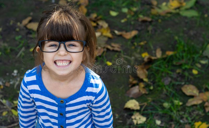 Cute kid in glasses smiling and looking at camera. Child with blue big eyes, brunette hair, white teeth. royalty free stock photography