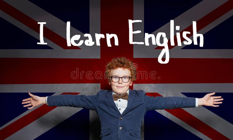 Cute kid in glasses on the UK flag background. Learn English concept royalty free stock photography