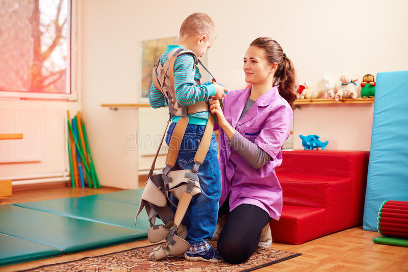Cute kid is going to have physical musculoskeletal therapy in rehabilitation center stock photos