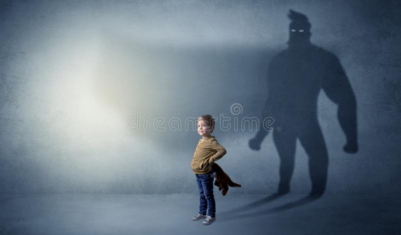 Cute kid with hero shadow behind. Cute kid in a room with plush on his hand and hero shadow on his background stock photos