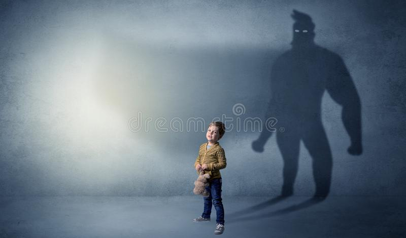 Cute kid with hero shadow behind. Cute kid in a room with plush on his hand and hero shadow on his backgroundn stock image