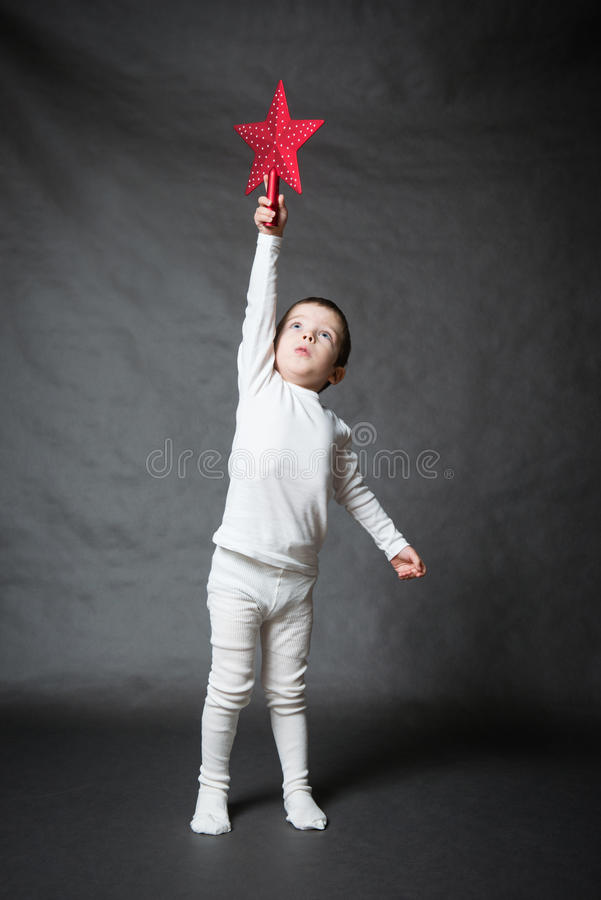 Cute kid holding red star. Cute kid in white holding red star, gray background royalty free stock images