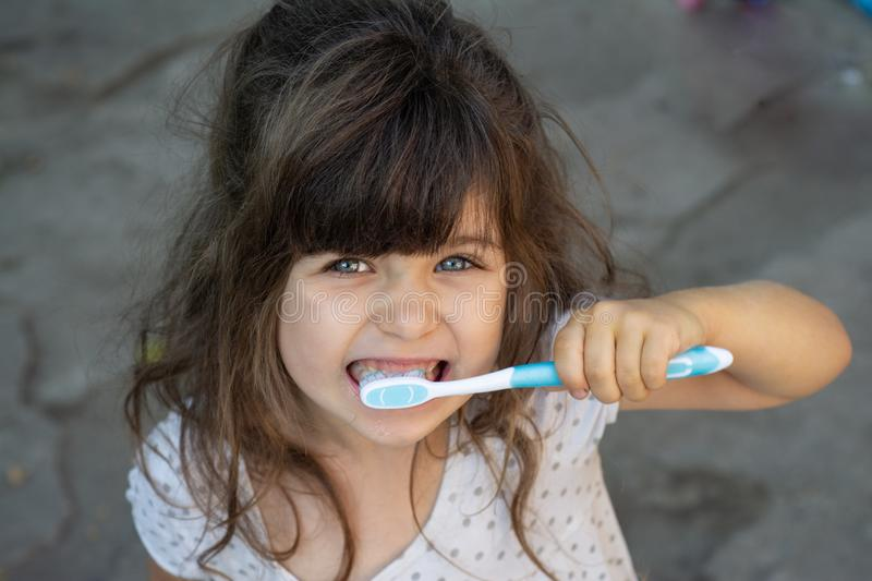 Cute kid holding a toothbrush in her hand and brushing teeth. stock photo