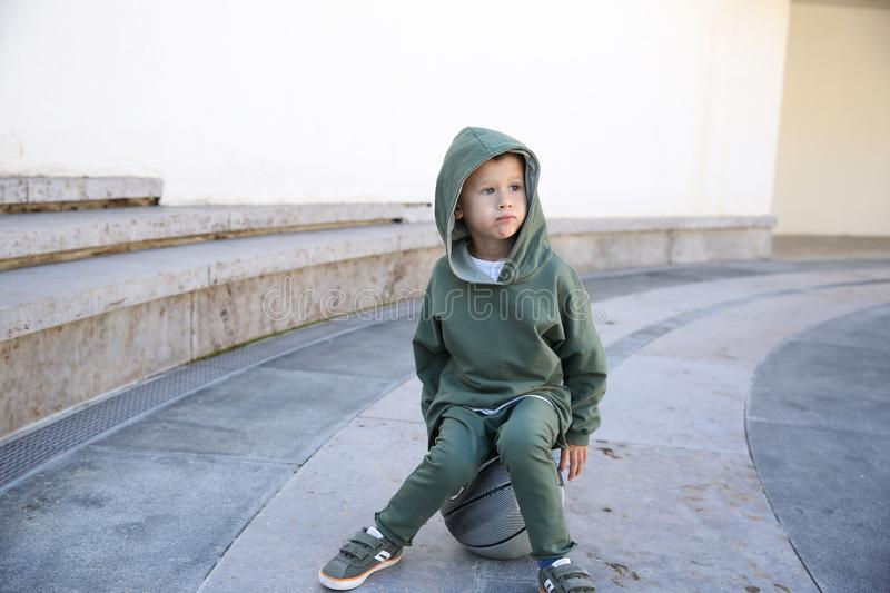 Cute kid at the hoodie sitting on the ball in the park stock images