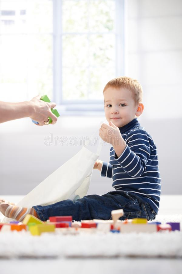 Cute kid packing toys to plastic bag. Playing at home on floor stock photo