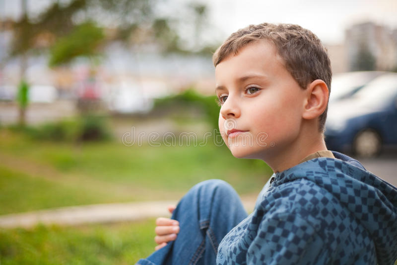 Cute kid in a park. Cute kid sitting in a park royalty free stock images
