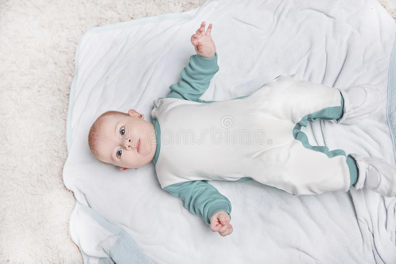 Cute kid in a penguin suit lying on a blanket. Photo with space for text stock photo