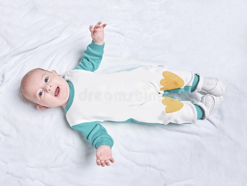 Cute kid in a penguin suit lying on a blanket. Photo with space for text stock images