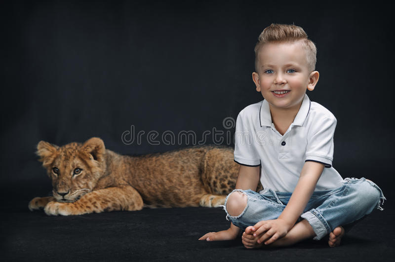 Cute kid playing with a lion cub on a black background. Cute children playing with a lion cub on a black background royalty free stock photos
