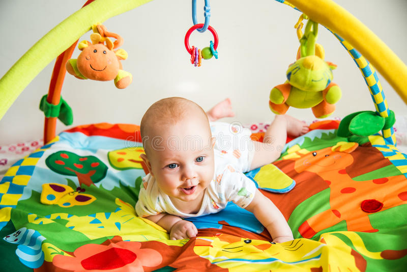 Cute kid playing. Male infant playing on his soft colorful blanket with jungle animals royalty free stock photo