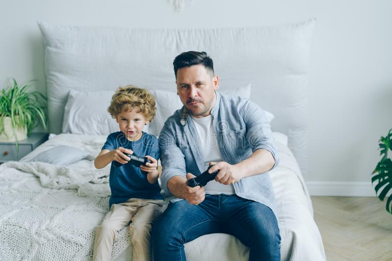 Cute kid playing video game with father holding joysticks having fun in bed royalty free stock photography