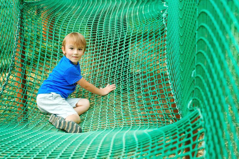 Cute kid plays at outdoors playground. Modern rope adventure park. Happy childhood. Happy summer holidays royalty free stock image