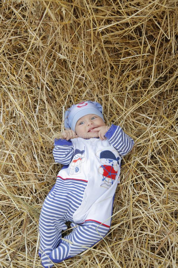 The child lies in a stack of straw in a bunny suit and smiles cute stock image