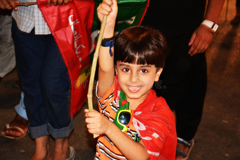 Cute Kid at Raiwind March – 30 September 2016. A cute kid holding PTI Flag and smiling. Pakistan Tehreek E Insaf was running a movement against prime stock image