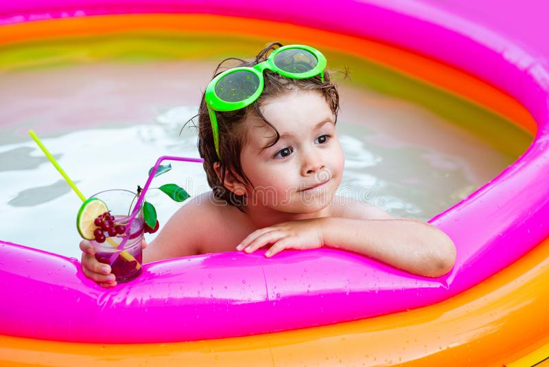 Cute kid relaxing on swimming pool. Maldives or Miami beach water. Happy little boy playing in swimming pool outdoor on royalty free stock image
