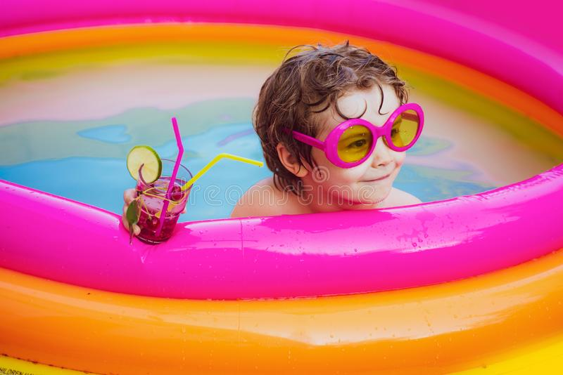 Cute kid relaxing on swimming pool. Smiling cute little boy in sunglasses in pool in sunny day with colorful tropical royalty free stock photography