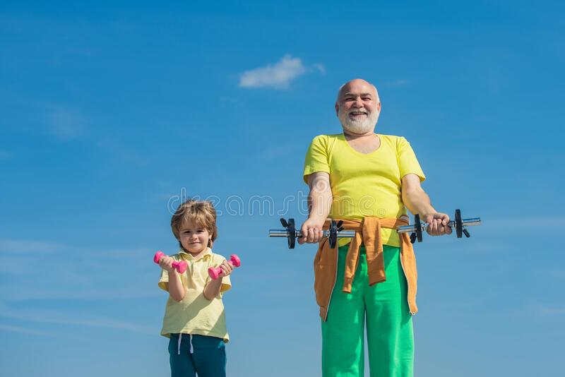 Cute kid and senior man exercising with dumbbells. Sports coach and kid building strength with dumbbells. royalty free stock photos