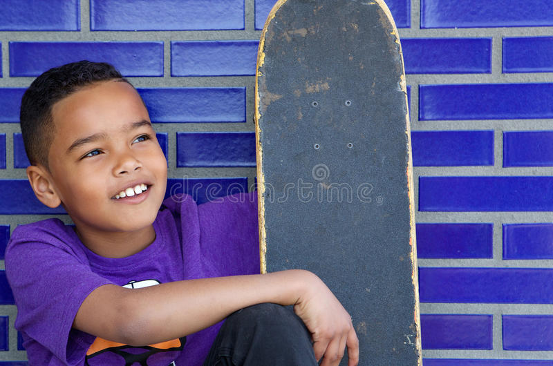 Cute kid smiling outdoors with skateboard stock image
