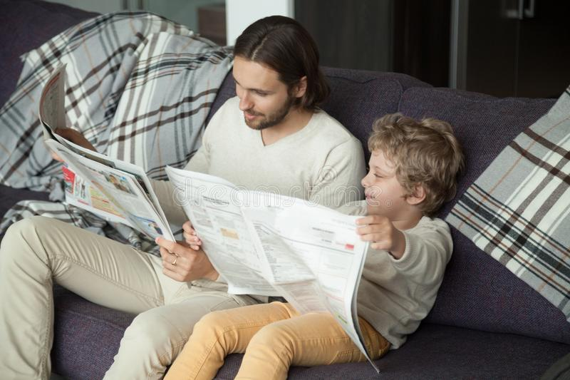 Cute kid son reading newspaper sitting on sofa with dad stock image