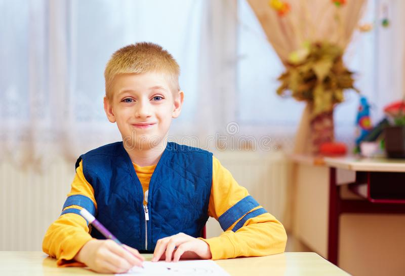 Cute kid with special need sitting at the desk in classroom. Cute kid, boy with special need sitting at the desk , writing in notebook in classroom stock photos