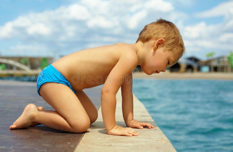 Cute Kid Squats On Pier And Looks In Water Royalty Free Stock Photo