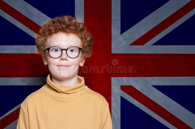 Cute kid student against the UK flag background. Learn English concept stock images