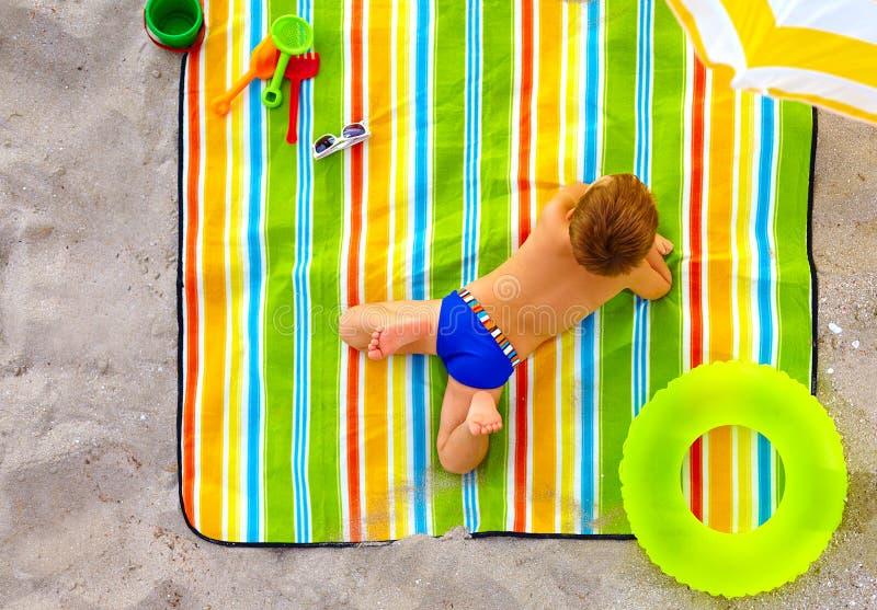 Cute kid sunbathing on colorful beach royalty free stock photo