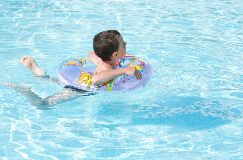 Cute kid swimming in pool stock photos