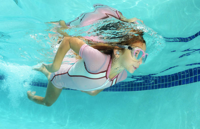Cute kid swimming in pool royalty free stock photography