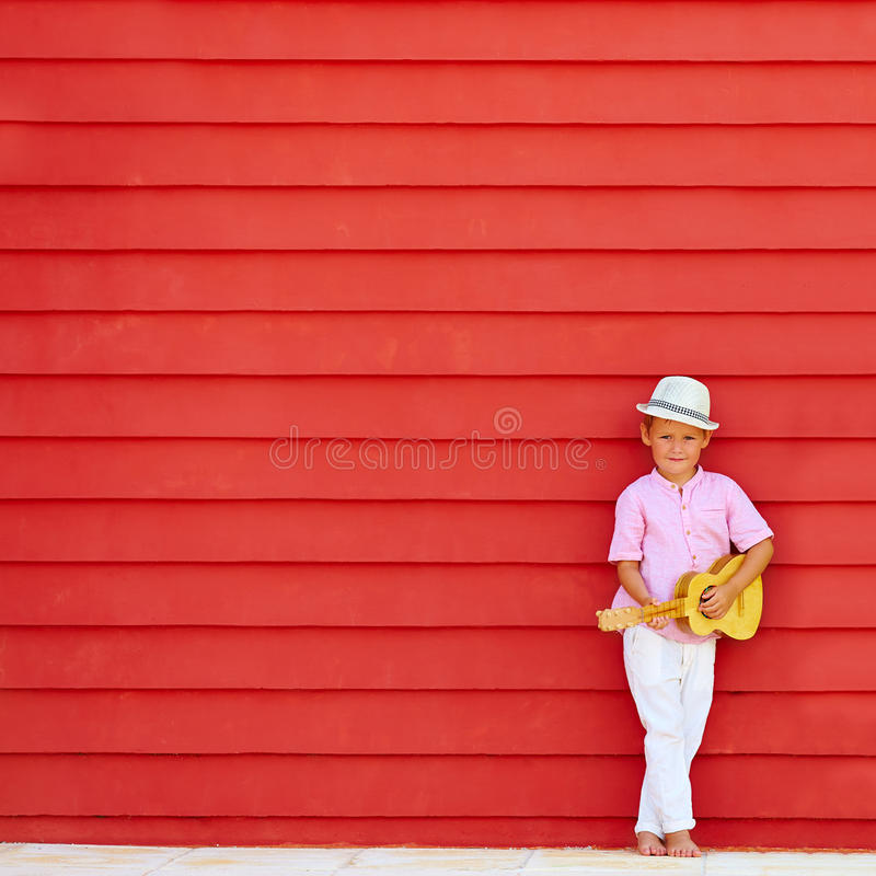 Cute kid with ukulele play music near the colorful wall. Cute boy, kid with ukulele play music near the colorful wall royalty free stock image