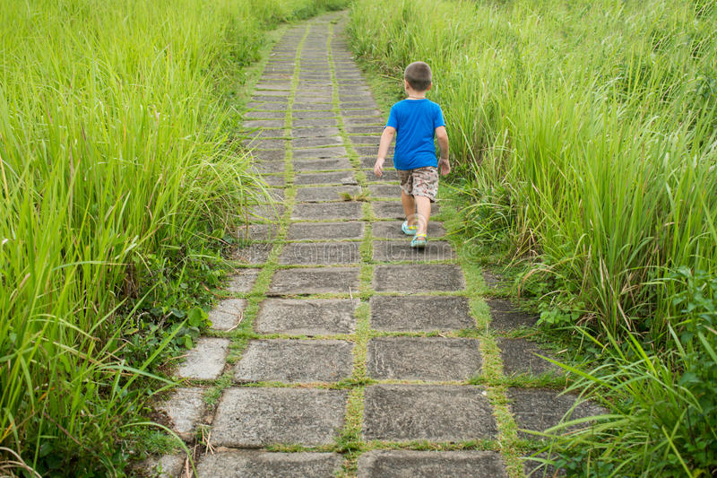 Cute Kid walking alone outdoors. Cute Kid walking alone outdoors royalty free stock images