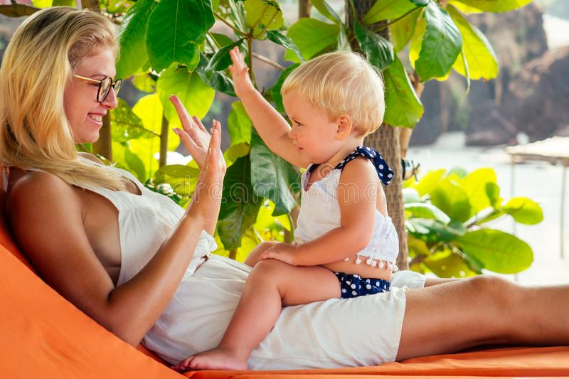 Cute kid and young blonde female parent playing hide and seek making a joke.Woman and little fair-haired girl year old. Baby on beach against a background of royalty free stock photography