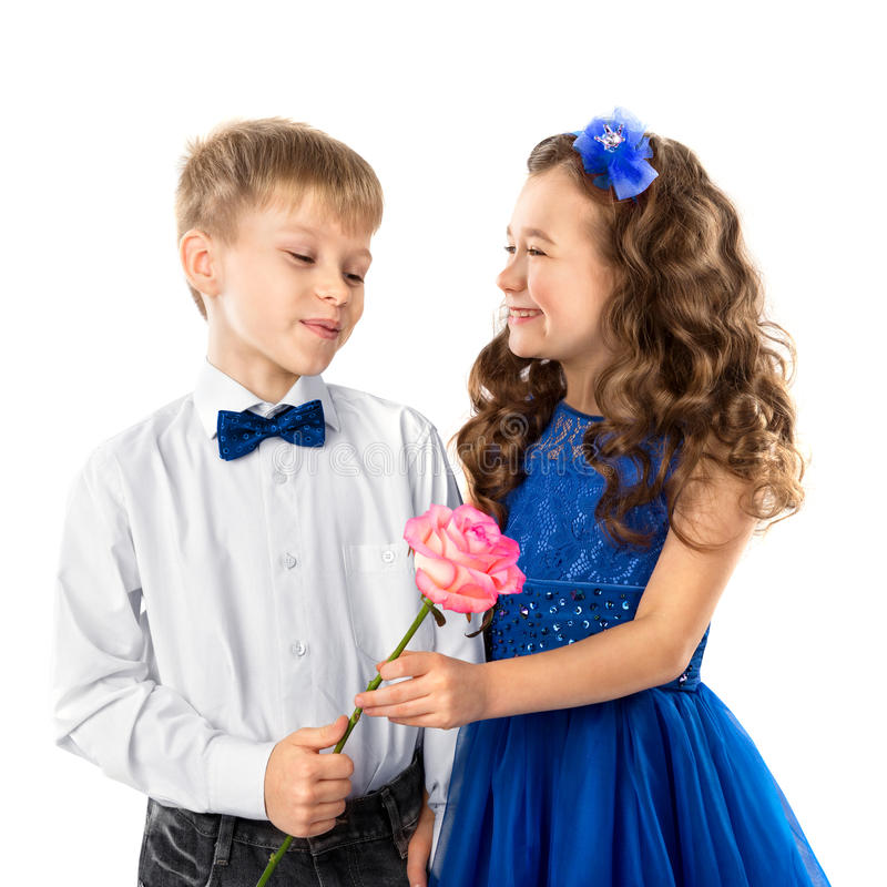 Cute kids, boy gives a flower little girl isolated on white. Valentine`s Day. Child love royalty free stock photo