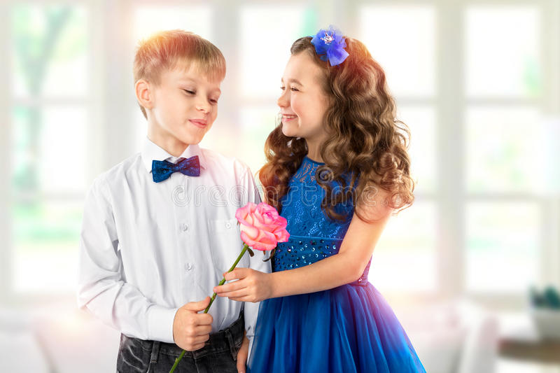 Cute kids, boy gives a flower little girl. Valentine`s Day. Child love. Cute kids, boy gives a flower beautiful little girl. Valentine`s Day and Women`s Day royalty free stock photo