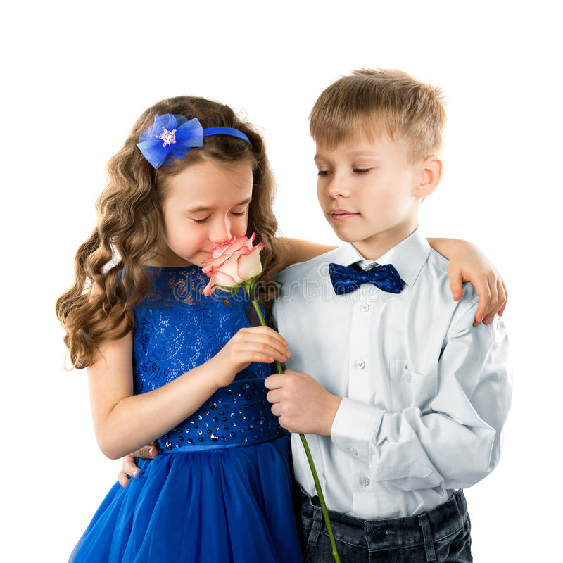 Cute kids, boy gives a flower little girl. Valentine`s and Women Day. Child love. Cute children, boy gives a flower beautiful little girl. Kids isolated on white royalty free stock photos