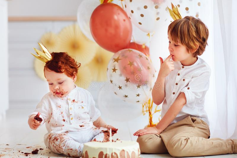 Cute kids, brothers tasting birthday cake on 1st birthday party. Cute kids, brothers tasting birthday chocolate cake on 1st birthday party royalty free stock photos