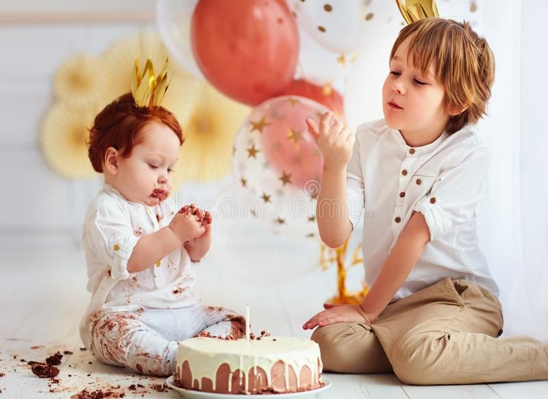 Cute kids, brothers tasting birthday cake on 1st birthday party stock images