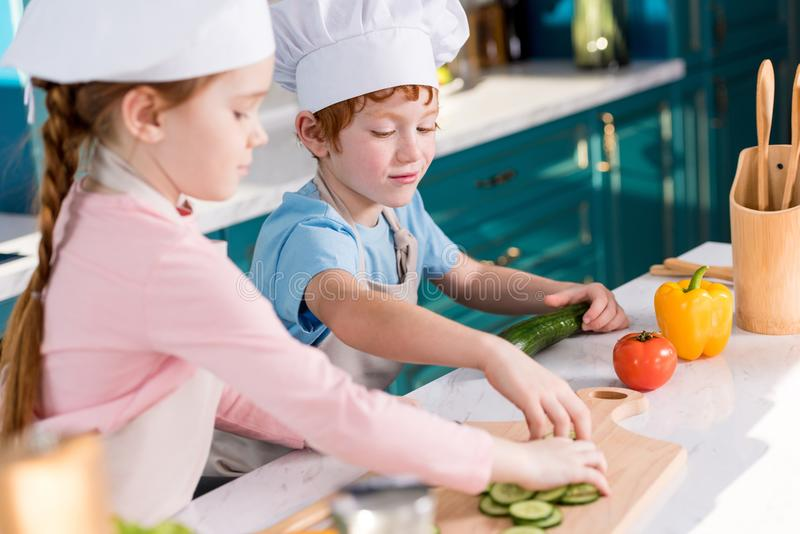 Cute kids in chef hats and aprons preparing vegetable salad together. In kitchen royalty free stock photos