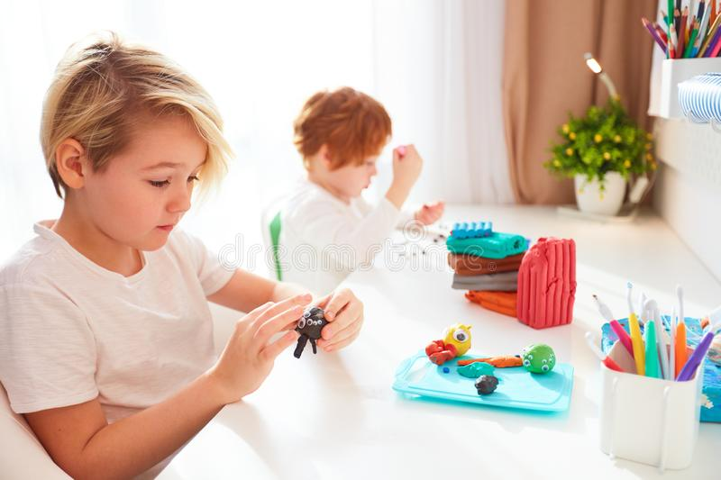 Cute kids are creating the hand crafts from modelling plasticine at kids room. Two cute kids are creating the hand crafts from modelling plasticine at kids room royalty free stock photo