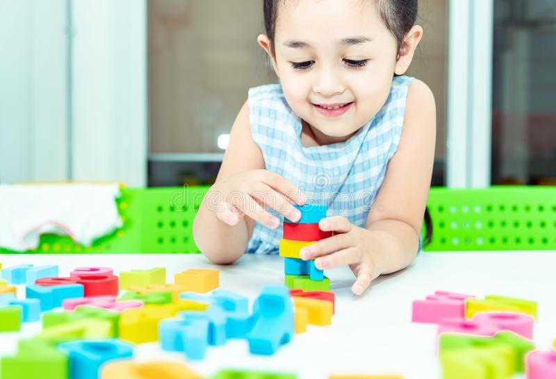 Cute kids female playing with toy designer on the floor at home. Child girl exciting while playing with alphabet colorful blocks. stock photos