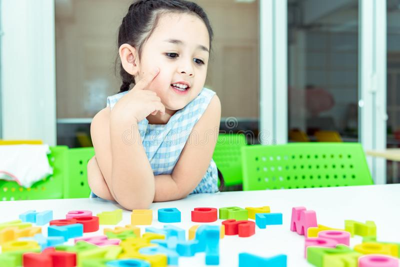 Cute kids female playing with toy designer on the floor at home. Child girl exciting while playing with alphabet colorful blocks. royalty free stock image