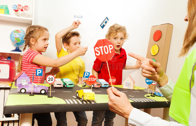 Cute kids having fun teaching traffic signs. Group of three kids, preschool boys and girl having fun teaching traffic signs and female teacher pointing to a Stop stock images