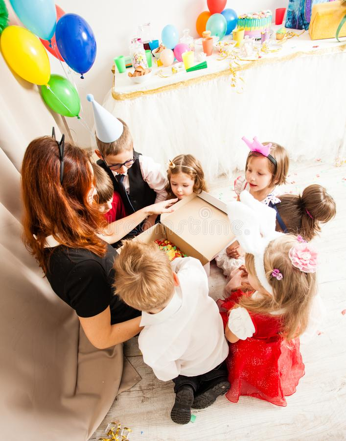 The games with animator. Cute kids playing with animator on the birthday party. Cat women entertains the guests stock images