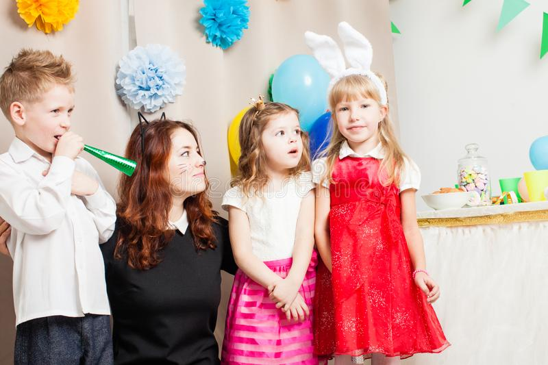 The games with animator. Cute kids playing with animator on the birthday party. Cat women entertains the guests royalty free stock images