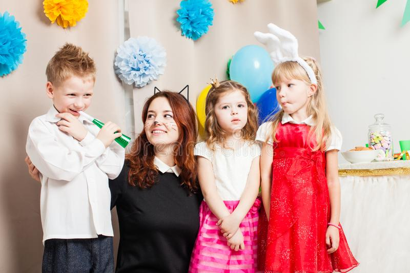 The games with animator. Cute kids playing with animator on the birthday party. Cat women entertains the guests royalty free stock photography