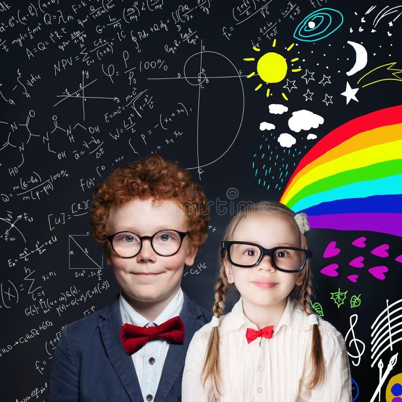 Cute kids portrait. Smiling school girl and boy on blackboard background royalty free stock photo