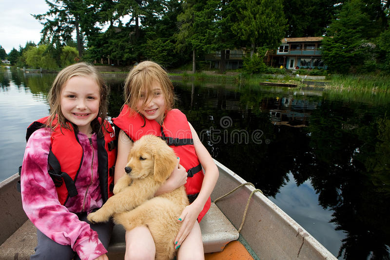 Cute kids and a puppy on a lake royalty free stock image